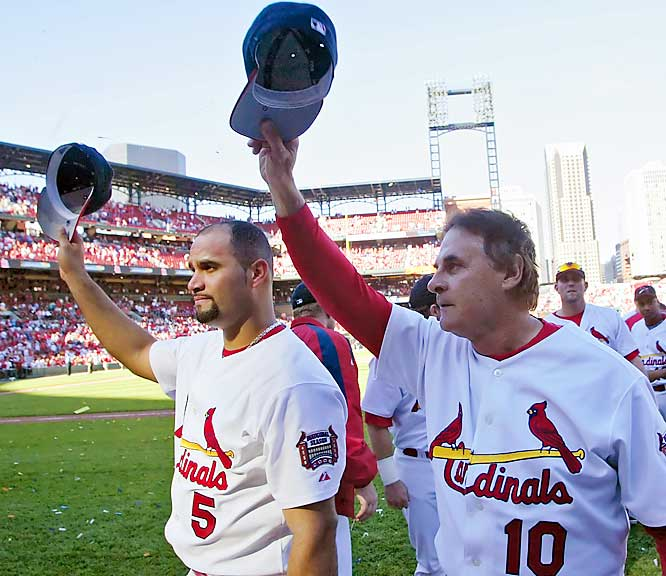 The Cardinals' Albert Pujols (left) and manager Tony La Russa salute the fans after clinching the NL Central title on Sunday, despite losing 5-3 to the Brewers.