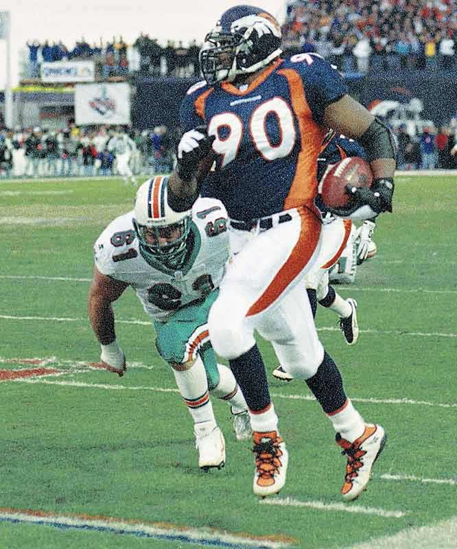 Defensive lineman Neil Smith recovered a Miami fumble and returned it 79 yards for his first postseason touchdown, driving the Broncos' lead to 38-3 and giving Denver its fifth-consecutive postseason win.