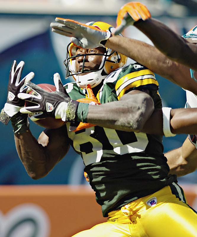 Green Bay receiver Donald Driver pulls in a 34-yard touchdown pass from Brett Favre in the third quarter at Dolphin Stadium. An official initially ruled that Driver failed to maintain possession as he rolled into the end zone with two Miami defenders, but a replay overruled the call.