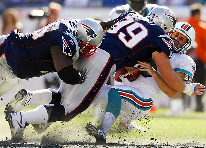 Patriots defensive lineman Mike Wright (99) and Vince Wilfork tackle Dolphins punter Donnie Jones after Jones recovered his own fumbled snap in the third quarter. The Patriots scored 17 points off three Dolphins turnovers.