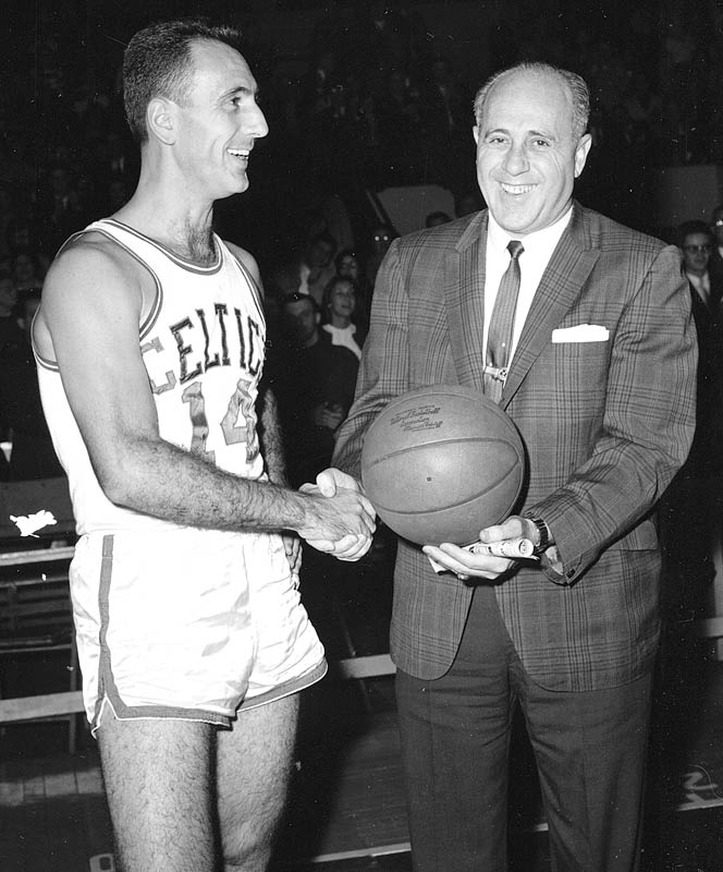 Bob Cousy (14) of the Boston Celtics is presented the basketball by Auerbach following a 1961 game at Boston Garden, where Cousy scored the 150,00th point in his NBA career.