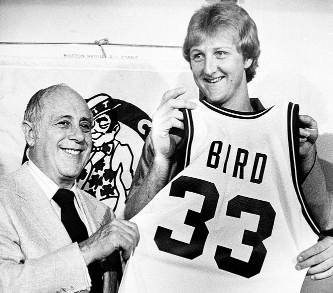 Former Indiana State basketball star Larry Bird holds up his new Boston Celtics uniform jersey with Celtics president Auerbach at a news conference in 1979.