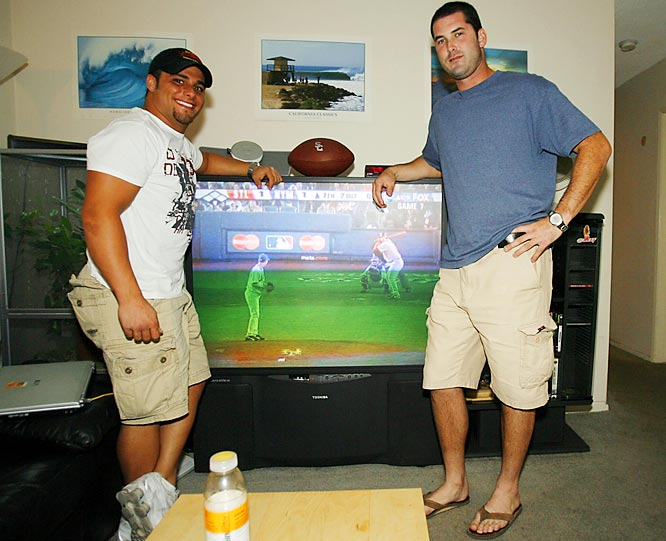"The main attraction of Booty's living room is a 60-inch television, which is showing Game 7 of the National League Championship Series. When a live ball game isn't airing, Booty pops in game tape to study.<rb.""This is where I spend most of my time,"" Booty says.<br><br>Here he is with his friend from high school, Aaron Savoie, who played running back on Booty's state championship teams in Louisiana."