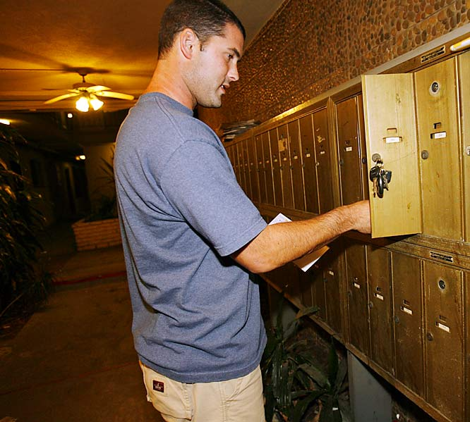 While USC quarterback John David Booty enjoys the limelight on Saturdays, he spends the rest of his time in a dingy two-story apartment complex about seven blocks north of campus. His place is as simple as a quarterback sneak. There's just a living room, kitchen, bathroom and two bedrooms. Andy Gui, a pitcher on the baseball team, lives in the other room. <br><br>Here, Booty checks his mail, just like any other student.