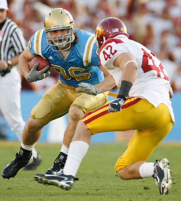 Tight end Logan Paulsen of UCLA put a move on USC linebacker Dallas Sartz.