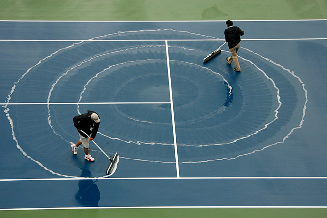 Sweepers create a hypnotic spiral while cleaning the courts at the 2006 U.S. Open.