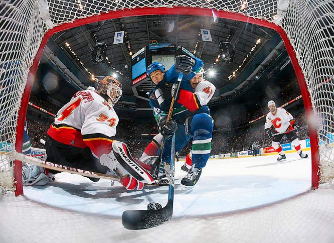 Mark Giordano (46) reaches for the puck while defending against Richard Park (18) of the Vancouver Canucks.