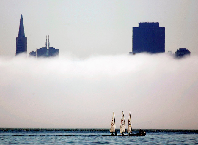 Sailboats make their way out toward the fog on San Francisco Bay.