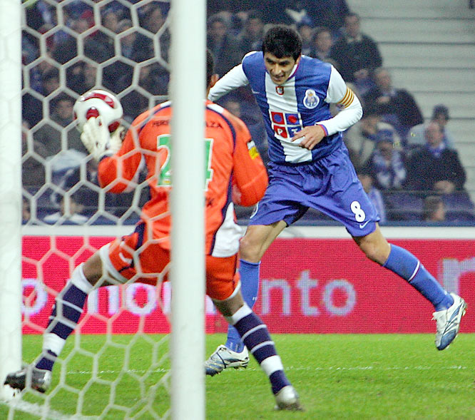 Argentine defender Lucho González (right) taps the ball past Paços keeper Peçanha as Portuguese heavyweight Porto continued its dominance atop the Liga. Porto has won seven straight and is gunning for its 21st league title.