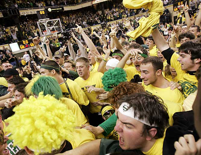 Oregon fans mob the floor after the Ducks defeated top-ranked UCLA, 68-66, on Saturday.