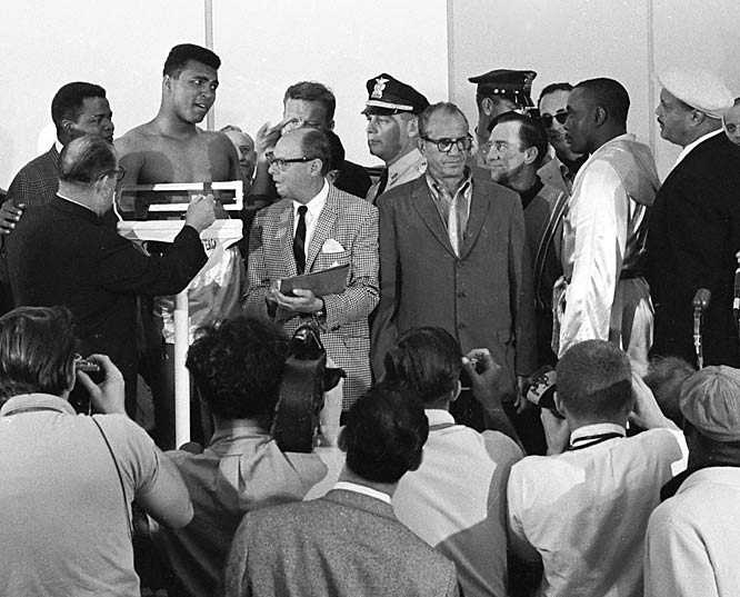 Weigh-in for the bout against Liston (in white, at right).