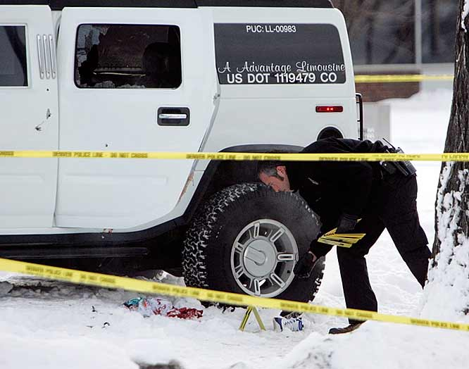An investigator with the Denver Police Department places evidence markers next to the Hummer limousine in which Denver Broncos cornerback Darrent Williams was riding inside of when he was shot and killed in the early morning on New Year's Day. Two other people in the vehicle were also shot in what police are calling a drive-by shooting. Bullet holes can be seen in the door and to the left of the door and the rear passenger window is shot out