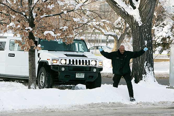 A Denver police investigator climbs over a snowbank next to a limousine involved in the shooting.