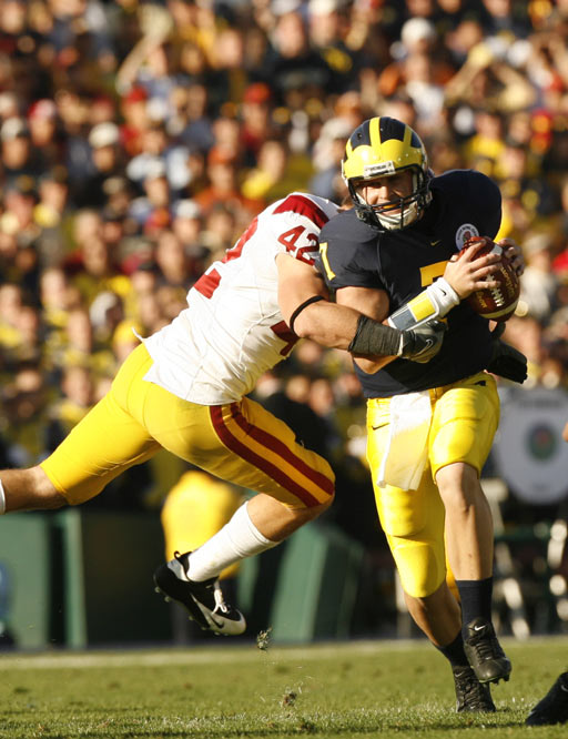 Linebacker Dallas Sartz of USC forces Michigan QB Chad Henne out of the pocket.