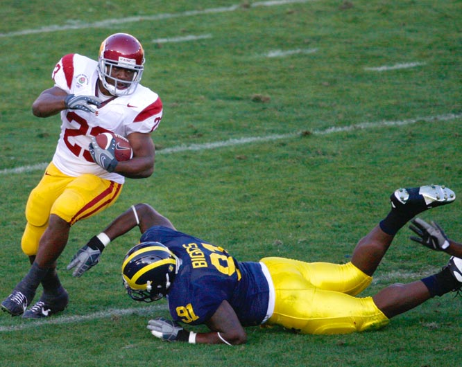 Chauncey Washington slips past Rondell Biggs of Michigan as he turns upfield in the 93rd Rose Bowl.