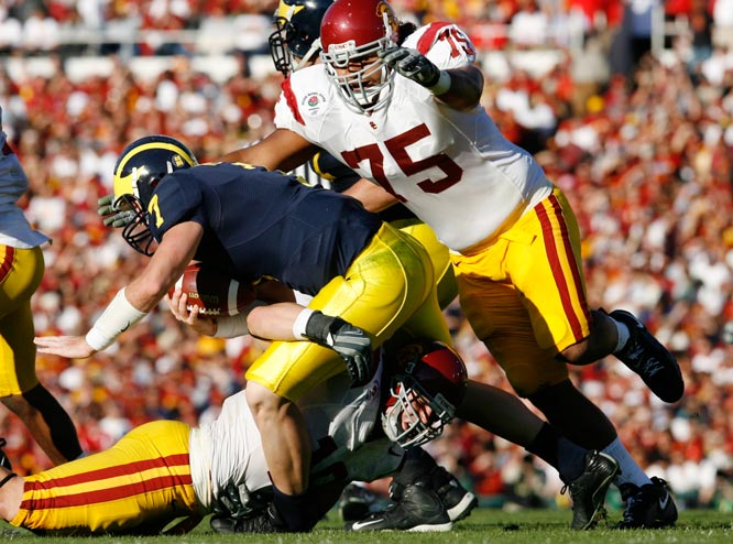 Fili Moala of USC piles on Michigan quarterback Chad Henne after linebacker Brian Cushing made the initial contact.