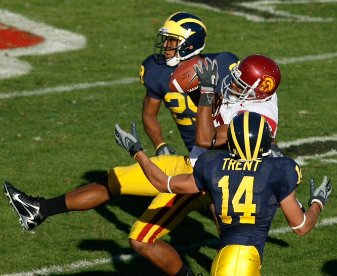 Tight end Fred Davis of USC hauls in a catch of a John David Booty pass between two Michigan defenders.