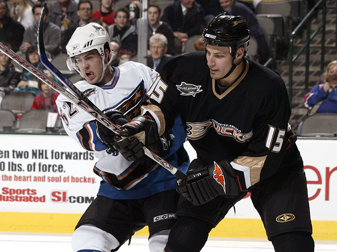 In a rare show of physical play, Mike Green (left) and Ryan Getzlaf fight for a loose puck.