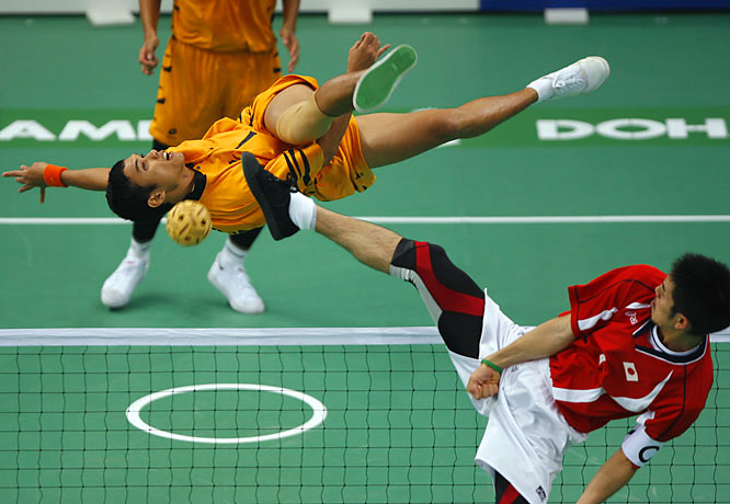 Mohd Azlan Abdul Mubin (orange) of Malaysia against Japan's Susumu Teramoto (red) during the men's Sepaktakraw team preliminaries.
