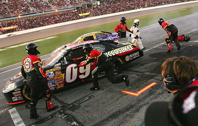 A crew member for Mike Wallace, driver of the No. 09 Chevrolet, holds his leg after being hit by Jamie McMurray, driver of the No. 26 Ford, in the pits. The crew member was treated and released.