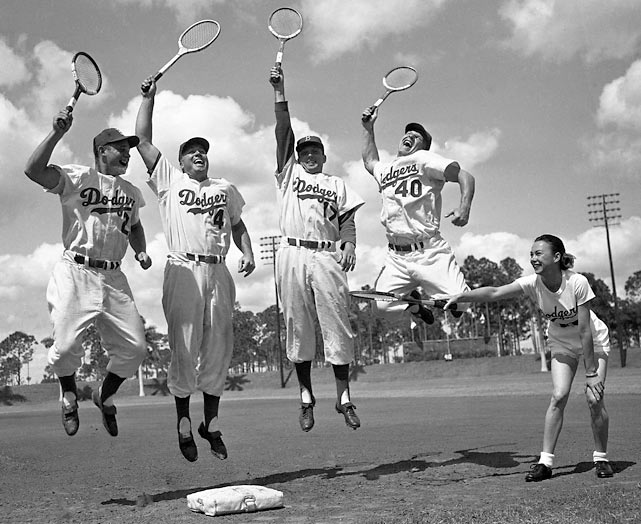 Tennis star Gussie Moran instructing Brooklyn Dodgers players on their tennis form in Vero Beach, Fla. Players pictured are Don Zimmer, Duke Snider, Carl Erskine, and Walt Moryn.