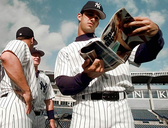 Jorge Posada checks out the SI Swimsuit issue during a break in the action.
