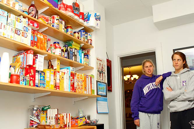Kristen Kjellman (left) and Emily Lovett contemplate the hundreds of boxes of oatmeal, different kinds of cereal, and peanut butter stock the downstairs kitchen.