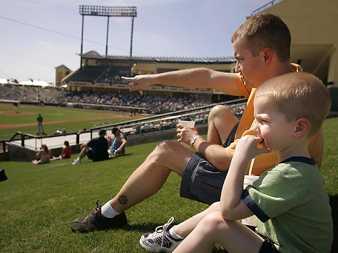 Alec Abera of Orlando, Fla., and his son, Evan, 3, watch a spring training game between the Braves and Georgia Tech on Feb. 28.