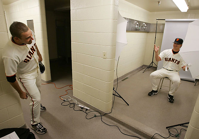 Pitcher Jack Taschner peeks at teammate Matt Cain as he has his picture taken in a clubhouse shower studio.