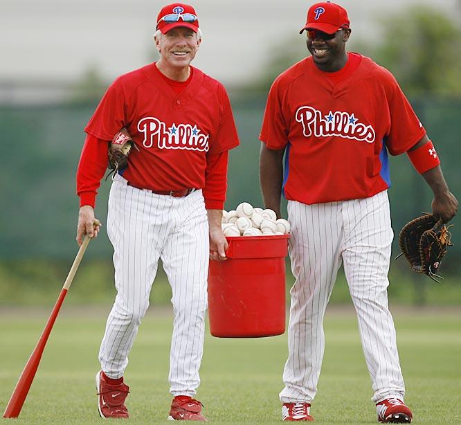 Phillies legend Mike Schmidt helps Ryan Howard carry a tub of balls.