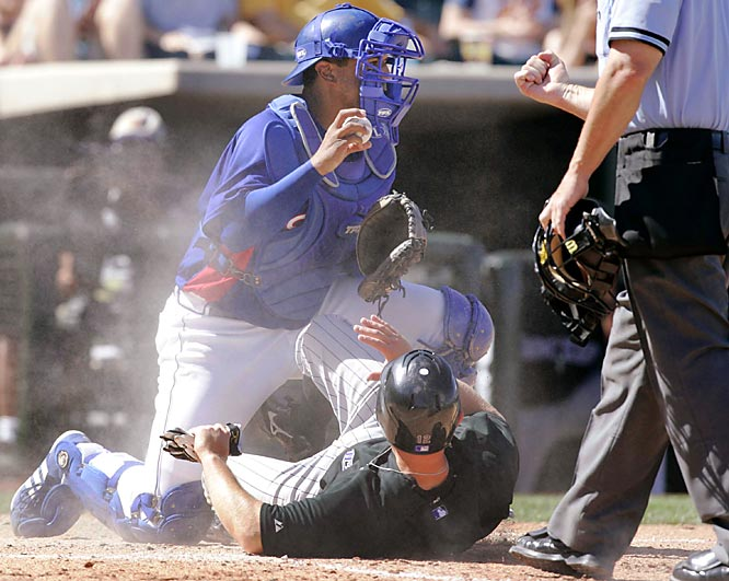 Home plate umpire Jim Wolf, right, signals the out as Rangers catcher Miguel Ojeda checks on the runner after the play on Clint Barnes.
