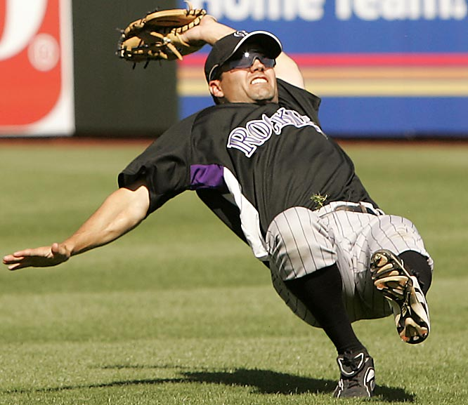 Jamey Carroll leaps backwards to make a catch after misjudging a pop-up in a game against the Rangers in Surprise, Ariz.