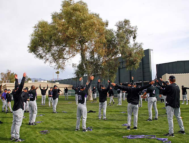 Pitchers and catchers begin their morning stretching exercises.