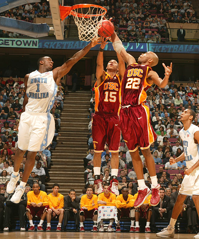 Taj Gibson (22) and Dwight Lewis (15) of USC fight for a loose ball against UNC's Marcus Ginyard.