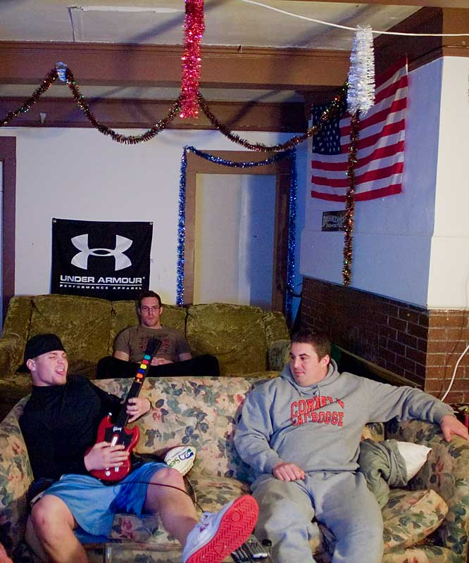 A stadium seating setup provides maximum TV viewing capacity.  Here, Todd Olson plays Guitar Hero to the ridicule of Tim Randall (right) and Brian Clayton (back). Note the holiday decorations in the back ... four months after the holiday season ended.