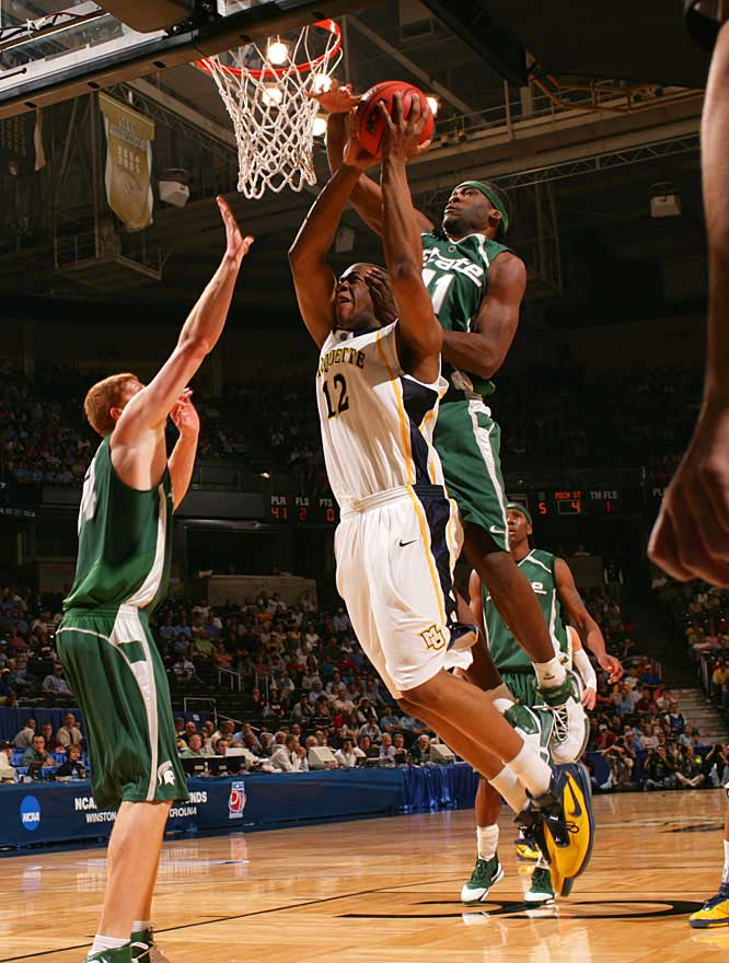 Marquise Gray blocks a shot by Marquette's Dwight Burke in the Spartans' victory.
