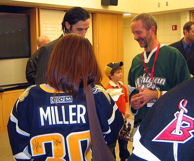 "Dr. Robert Stein (right), a veterinarian at Amherst Small Animal Hospital, and his daughter Ellina (left), snag an autograph from Sabres goaltender Ryan Miller. ""I'm always talking about the Sabres,"" says Stein. ""Even in the operating room."""
