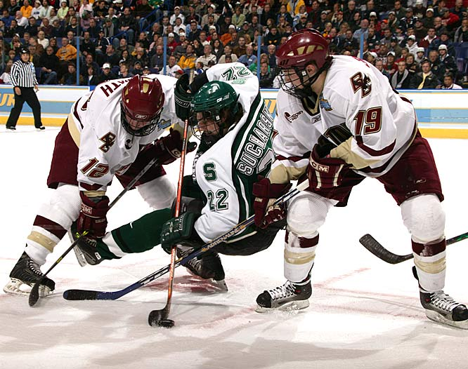 Michigan State forward Nick Sucharski (22) falls to the ice while trying to maintain possession of the puck after winning a face-off against Boston College forward Ben Smith (12).