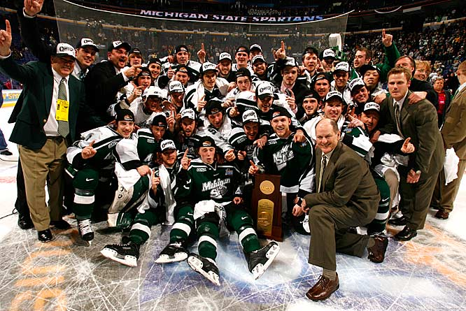 Michigan State players pose for a team photo with their championship trophy.
