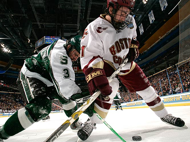 Michigan State defenseman Chris Snavely (3) and Boston College forward Benn Ferriero (21) fight for possession of the puck along the boards.