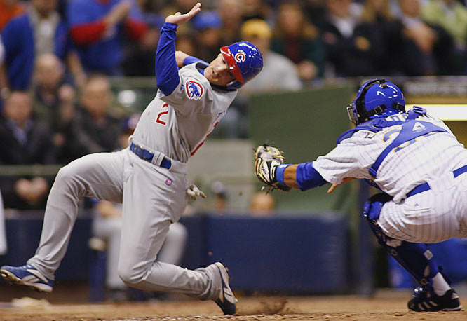 The Cubs' Ryan Theriot avoids the tag attempt by Brewers' catcher Johnny Estrada to score in the seventh inning on Friday.  Chicago won 9-3.