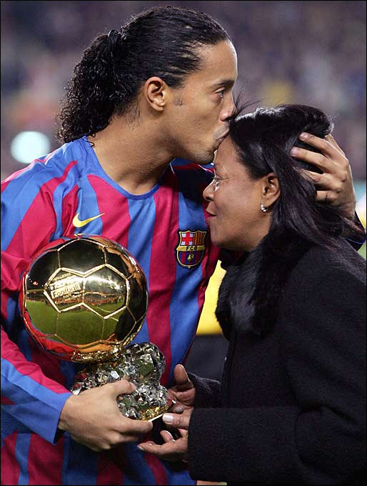 FC Barcelona's Ronaldinho kisses his mother, Miguelina, while holding his Ballon d'or (Golden Ball) trophy for best football player of the year.