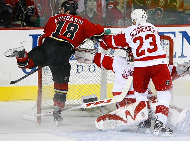 Center Matthew Lombardi jumps onto the net after scoring the Flames' first goal of the game on Dominik Hasek in the second period.
