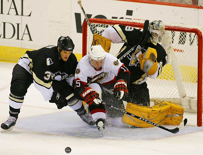 Pens' goalie Marc-Andre Fleury takes a stick to the face from teammate Mark Eaton, trying to defend against Dany Heatley.  Fleury's teammates caused him more harm than good at times, like Jordan Staal's accidental redirection for a Senators goal early in the first period.