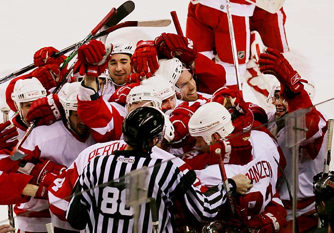 The Red Wings celebrate around teammate Johan Franzen after he scored early in the second overtime period to win the game and clinch the series 4-2.