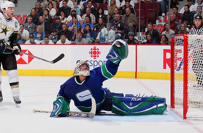 Stars captain Brendan Morrow and Canucks goalie Roberto Luongo watch a shot by the Stars' Mike Modano hit the crossbar, a goalie's best friend.
