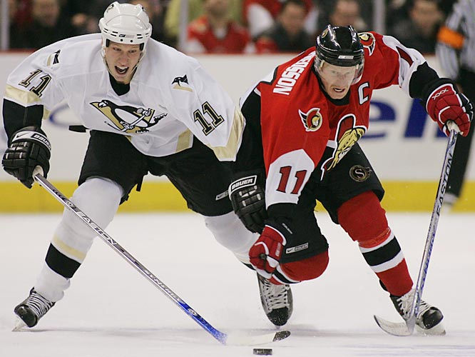Penguins rookie Jordan Staal vies for control of the puck with Senators winger Daniel Alfredsson.  Staal scored in his first career playoff game, while Alfredsson put eight shots on net for the Sens and earned the games number one star.
