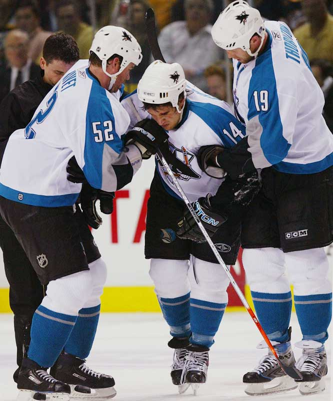 Craig Rivet and Joe Thornton help teammate Jonathan Cheechoo off the ice after a knee-on-knee collision with Predators forward Scott Hartnell.  Hartnell was given a five-minute major for kneeing and a game misconduct penalty.