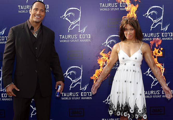 The Rock, shown here on the red carpet at the World Stunt Awards, doesn't seem fazed by the fact that Angela Uyeda  is on fire.