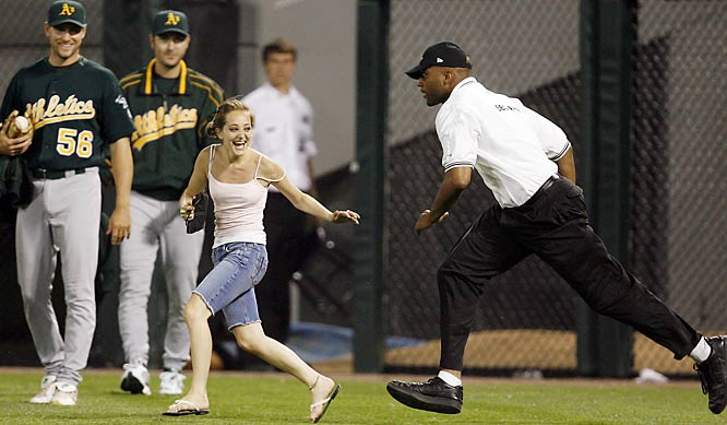 Funny. A's pitcher Lenny DiNardo (No. 56) doesn't seem to mind that this fan ran onto the field during Wednesday's A's-White Sox game.